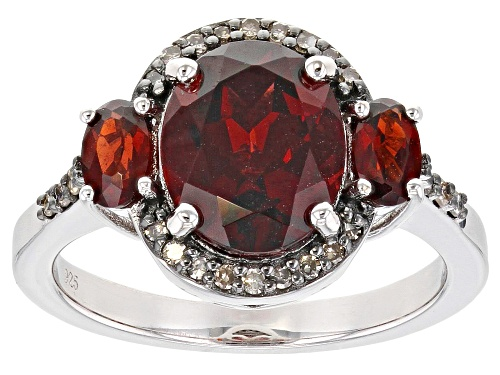 Photo of Pre-Owned 3.56ctw Oval Vermelho Garnet(TM) & .12ctw Round Champagne Diamond Rhodium Over Silver Ring - Size 7