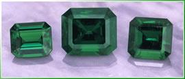 three loose emerald gemstones