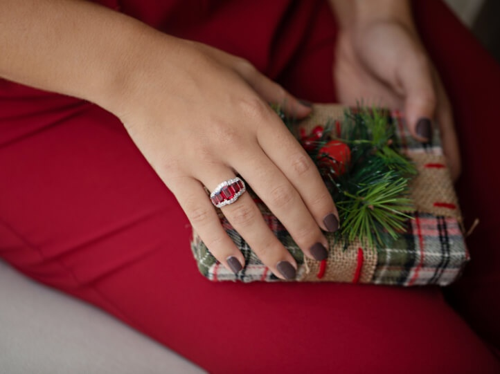 Woman wearing a ring holding a holiday gift box
