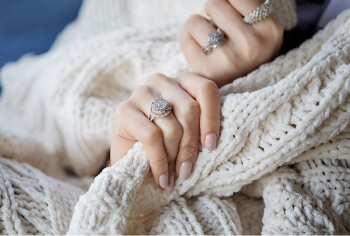 Woman holding a blanket wearing diamond rings