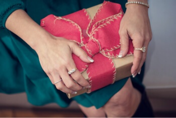 Woman wearing jewelry holding a holiday gift