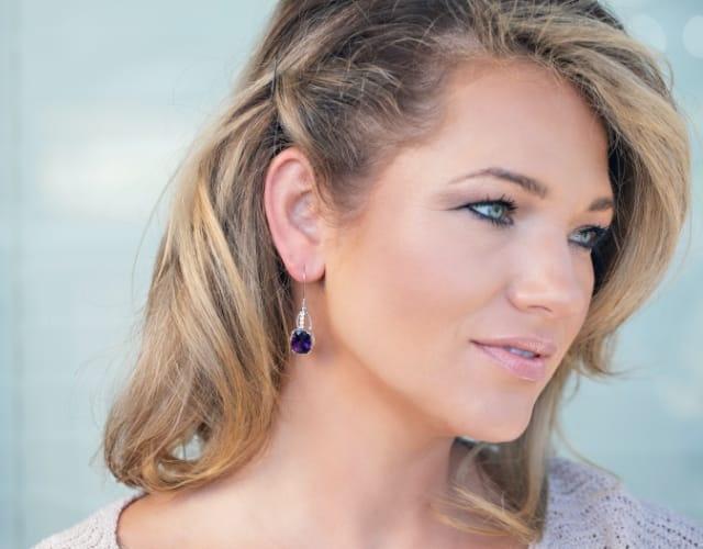 Woman wearing color gemstone earrings