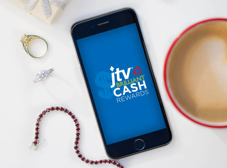 Brilliant Cash logo on a mobile phone surrounded by assorted jewelry and a coffee cup