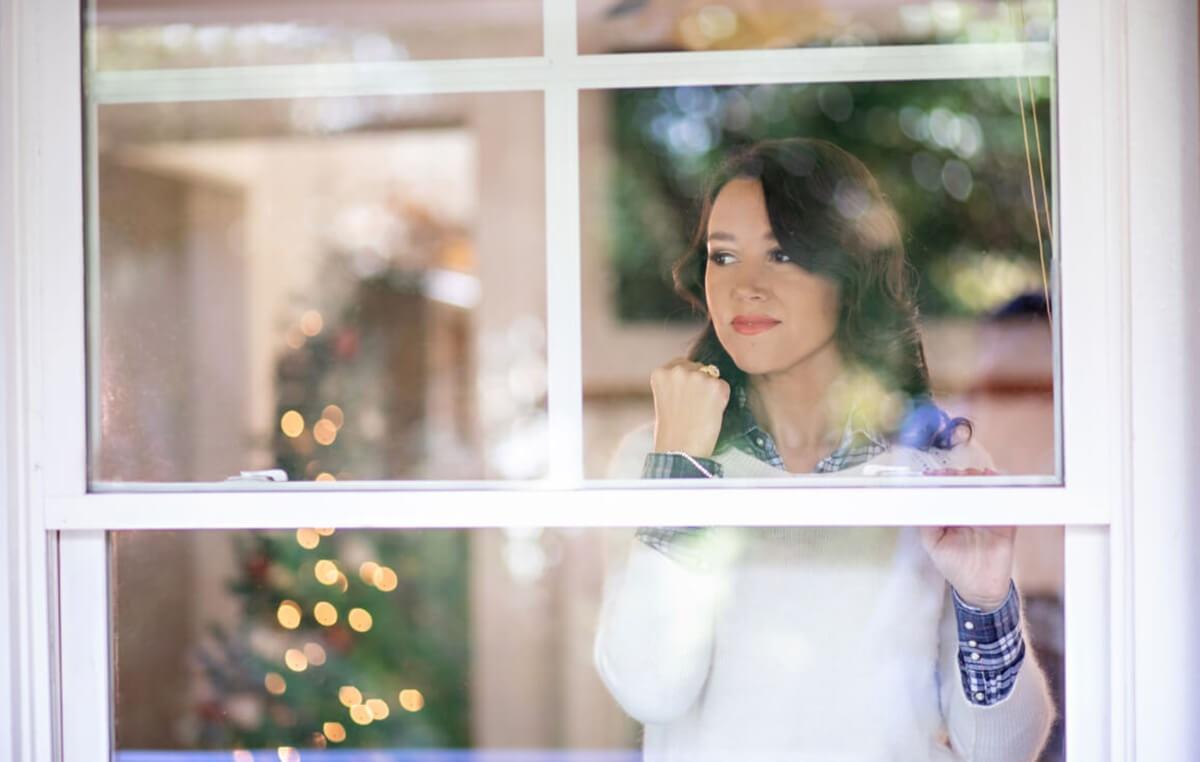 Woman wearing jewelry looking out a window