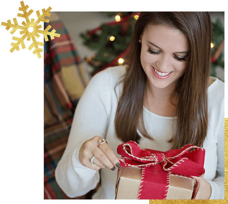 Woman wearing jewelry opening a holiday gift