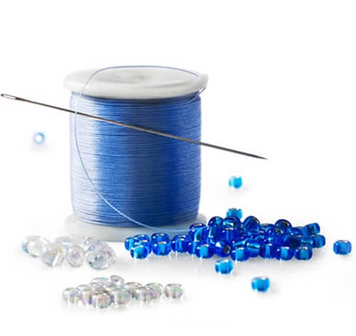 Needle, Spool of Blue Thread, Clear and Blue Beads