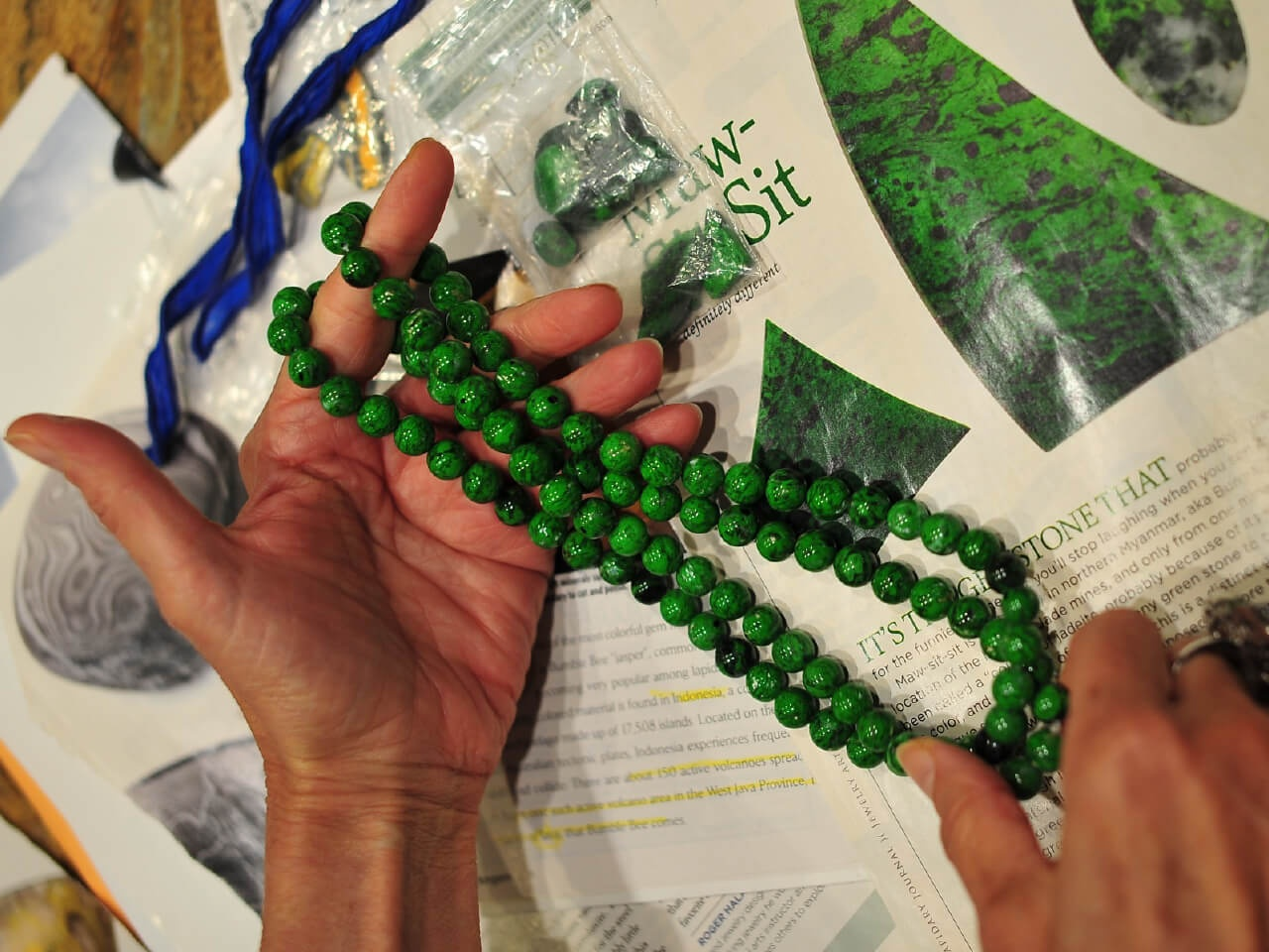 Hands holding a green necklace