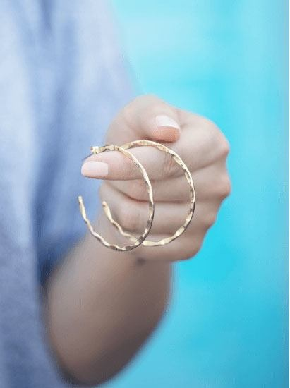 Woman holding gold hoop earrings