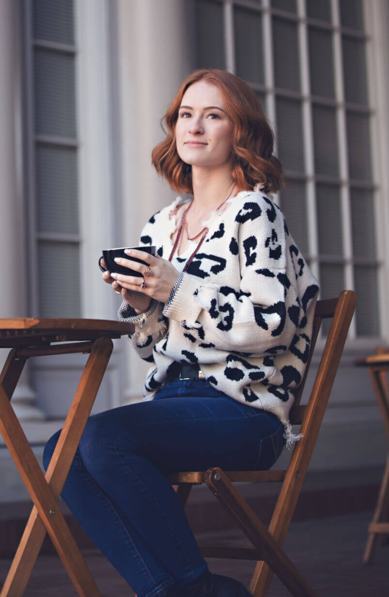 Woman wearing jewelry drinking coffee
