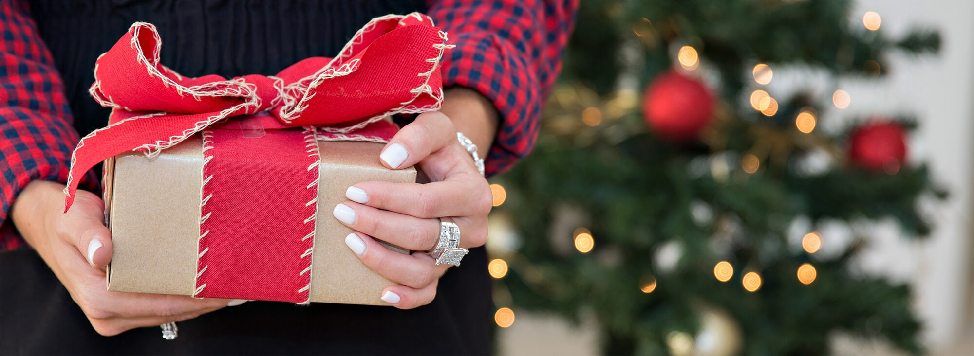 Woman wearing jewelry holding holiday gift